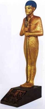 Ptah con un casquete, collar menat, cetro uas con el pilar Dyed y el Anj. Es de resaltar el extremo parecido de la estatuilla del Oscar con esta de Ptah.