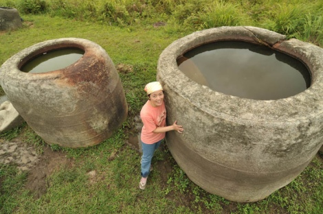 POSO, 14/9 - MEGALIT. Seorang wisatawan berpose diantara dua bejana batu raksasa (megalit) di Desa Besoa, Kecamatan Lore, Kabupaten Poso, Sulawesi Tengah, Senin (13/9). Megalit yang menurut sejarah dibuat pada zaman batu itu ramai dikunjungi wisatawan dan para peneliti dalam dan luar negeri. Selain bejana, terdapat pula patung manusia dari batu. Puluhan megalit di lokasi tersebut kini dikelola Dinas Kebudayaan setempat. FOTO ANTARA/Basri Marzuki/10