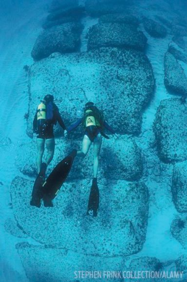 TWO SCUBA DIVERS EXPLORE THE BIMINI ROAD IN THE BAHAMAS